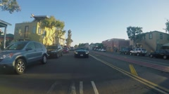 People in black car drive by Mission Boulevard at autumn - stock footage