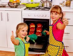 Children bake chocolate buns Stock Photos
