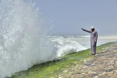 Local man watching the surf at the corniche of Salalah during the monsoon Stock Photos