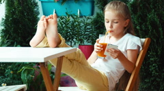 Girl drinking juice and using cell phone and smiling at camera Stock Footage