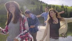 Carefree Teens Dance Down A Dock Toward Camera (Slow Motion) Stock Footage