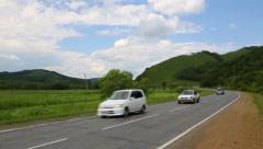 Cars drive on the road in a hilly area summer day. - stock footage