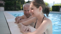 An elderly man talking to a young woman in the pool. summer fling Stock Footage