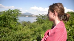Young woman admires the view of Lago Maggiore in the Italian Alps Stock Footage