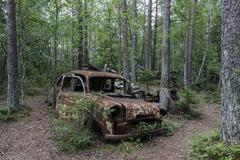 Junkyard in the forest junk car 40s at Ryd Smaland Sweden Europe Stock Photos