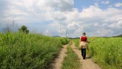 Lonely woman walking along a country road on a clear sunny day Stock Footage