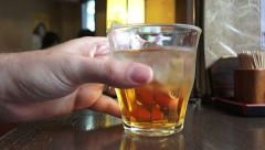 Hand Picks Up And Puts Down Glass Of Plum Wine With Ice At Tokyo Restaurant Stock Footage