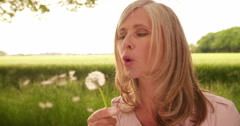 Mature woman blowing the seeds from dandelion in nature Stock Footage
