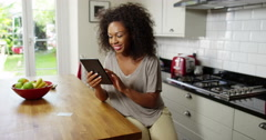 A cheerful woman doing her online shopping on a digital tablet Stock Footage