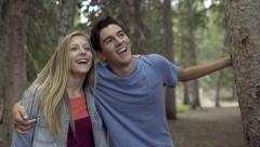 Cute Young Couple Rest Against Tree In The Forest, Smile And Hold Each Other Stock Footage