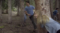 Teens Play Tag In Forest, Girl Falls Down And Laughs, Her Friends Help Her Up - stock footage