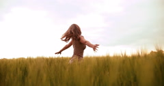 Mature woman spinning happily in wheat field - stock footage