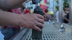 Filling up bottles with drinking water - stock footage
