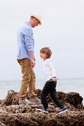 father and son playing outdoor on beach summer vacation - stock photo