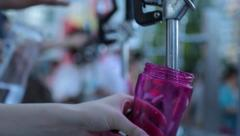 Pouring water into reusable plastic bottles - stock footage
