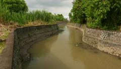 Stone walled canal banks, unnamed river near with Jl Gn Soputan bridge Stock Footage