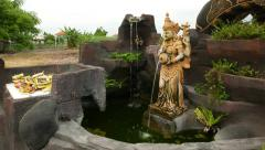 Tiny waterfall pond, Balinese Temple, Hindu sculpture with water stream from jug Stock Footage