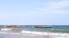 Little fishing boats by the shore in ocean waves in Thailand Stock Footage
