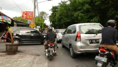 Traffic jam on balinese street, walk through sideway, car stand in line Stock Footage