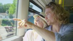 Young man shows his partner whats outside the window of a train in slow motion Stock Footage