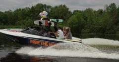 Ride the wave - Wakeboard boat full of party people headed out to the water Stock Footage