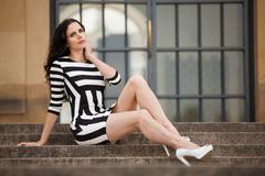 Stock Photo of beautiful woman in sexy dress on stairs summertime
