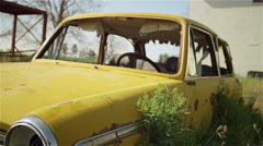 An old broken down car sits abandoned in a field Stock Footage
