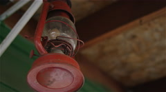 An old red lantern hanging from a porch Stock Footage