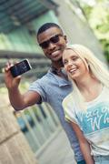 young smiling multiracial couple taking foto by smartphone - stock photo