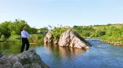 Businessman meditate near nice river . 4K 3840x2160 - stock footage