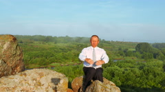 businessman sits at mountain top and meditate. 4K 3840x2160 - stock footage