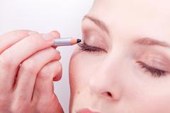 At the cosmetic studio eyeliner on eyes make up Stock Photos