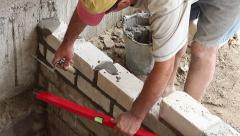 Builder building level checks the validity brick masonry in the new house Stock Footage