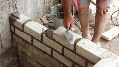 Work puts white silicate brick on cement misalignment Stock Footage
