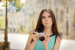 Undecided Girl with Compact Digital Camera Stock Photos