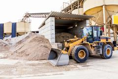 Stock Photo of Parked pay loader near pile of dirt