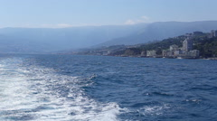 The boat leaves the ripples on the water passing by the coast of the southern Stock Footage