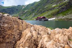 Idyllic view with cottege on Balea Lake shore in Fagaras Mountains Stock Photos