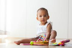 Portrait of little African American little girl sitting on the floor and play Stock Photos