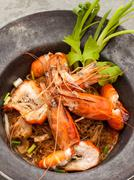 Baked king prawn vermicelli with soya sauce in hot pot. Stock Photos