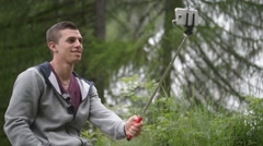 Stock Video Footage of Boy do selfy against the backdrop of a waterfall Cascata del Toce in Alps