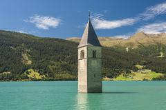 Steeple bell tower of the submerged church of the village of AltGraun in Lake Stock Photos