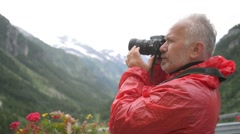 Alps - Male photographer taking pictures against the background of mountains Stock Footage