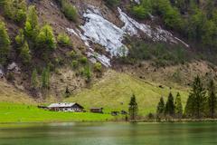 Farm house on mountain lake Obersee lake in spring. Bavaria, Germany - stock photo