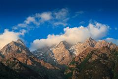 Himalayas mountain top summits in clouds on sunset - stock photo