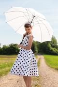 fifties look with petticoat dress, hairband und sunshade in the nature - stock photo