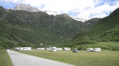 Motorhome parking on the background of snow-capped Alps Stock Footage