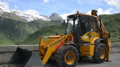 Excavator on the background of snow-capped Alps Stock Footage
