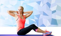 Stock Photo of smiling woman doing sit-up on mat over low poly