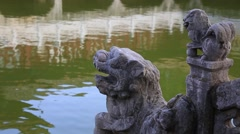 Stone lion standing against the pond of Yuantong Temple in Kunming Stock Footage